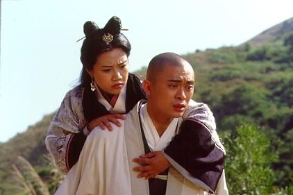 A photo of Xu Zhu carrying a young woman on his back as he walks past a hill.