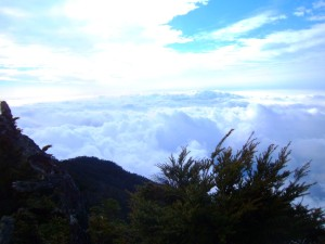 A cloud sea below the ridge, with high-level clouds above