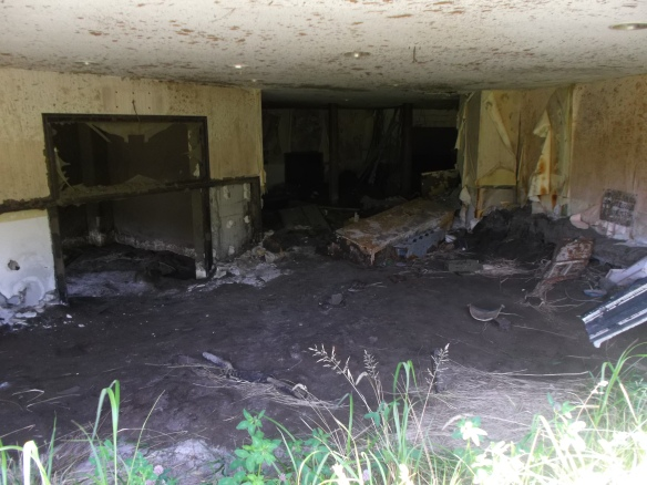 We look into an abandoned building which has a layer of volcanic silt covering the floor, with broken windows, appliances, etc lying around.  In the foreground we see a little grass.