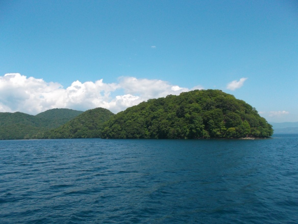 We see a clear blue sky above, with some low lying white clouds in the distance.  In the center we see forested islands in the lake.  The bottom half of the picture is all blue, blue lake.