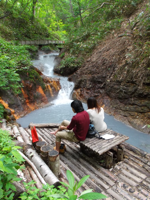 In a bright gree forest, we see a small waterfall of grey-blue water.  In the foreground is a little bamboo platform, with two people sitting on a little bench, with their backs facing the viewer.