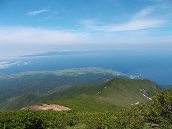 There is a green mountain ridge sloping from the bottom-left of the picture to the center-right of the picture.  Below the mountain ridge, in the flatlands we see a green forest which meets with a lighter green fringe right at the coastline, with a small airport visible.  Beyond the coastline, there is the ocean, and we can see the thin line of Rebun island in the center-left of the photo.  There are many clouds hovering above Rebun island, but at the very top of the picture, we can see the blue sky.