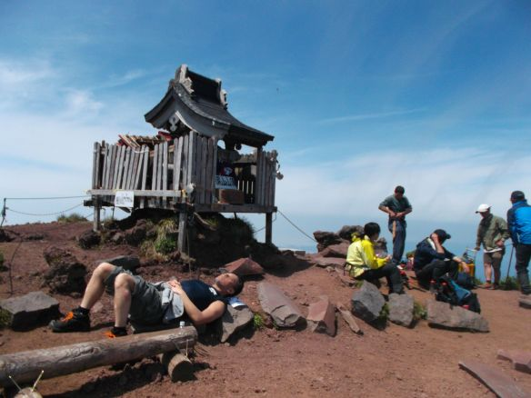 We see a blue sky with some white clouds hovering below.  On the center-left, we see a small Shinto shrine at a diagonal, with the left-front corner facing us.  A guy is lying down on volcanic rock between the viewer and the shrine.  To the right of the shrine a group of people are sitting down, with one standing up, relaxing and eating lunch.