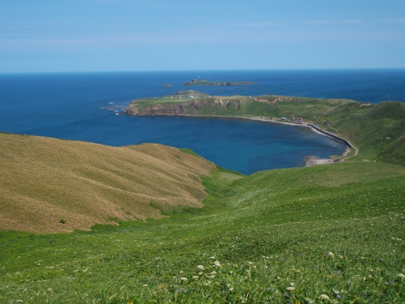 In the lower-left there is a yellow hill, and in the lower right there is a green slope going downwards. There is a cape curving around a blue bay like a hook.  Past the cape, there is a very small island.  Above the island, we see the sea, and a clear sky above.