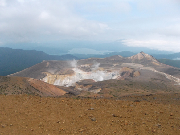 In the upper part of the picture we see a sky filling with clouds.  Below that, we can see through the haze Lake Akan and Mt. Oakan, which will soon be overtaken by clouds coming from the right.  Below that, we see a volcanic cone on the right, and a pit full of volcanic gas and steam amid white and reddish-brown rock.  Closest to the viewer is brownish-red crumbly ground.