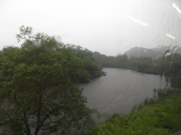 The sky above is white.  We can see that this photo was taken through a window with raindrops on it.  There are trees and greenery around a wide river making a bend towards the left.