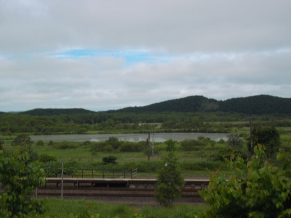 It is a mostly cloudy sky above, but a sliver of blue sky is seen.  In the distance are green forested hills, and beneath is a lake.  Closer to the viewer is a train platform amid the greenery.