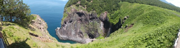 In this panorama shot, on the left we see some trees right above a cliff which is plunging into the blue sea.  Then we see a exposed rocky cliff further away also descending sharply into the blue sea.  There is a small, narrow little bay below it.  At the most inward part of the bay, we see a waterfall in the shadows, coming down a grassy cliff like a drooping tongue.
