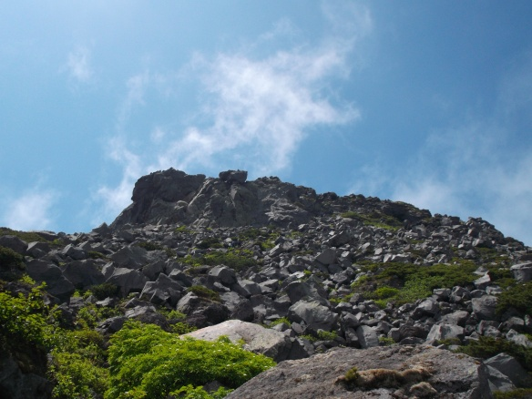 We see a clear blue sky with wisps of clouds coming up like smoke.  In the lower part of the picture, see what looks like an amazingly large flatish pile of grey rocks, which is in fact a mountain peak.