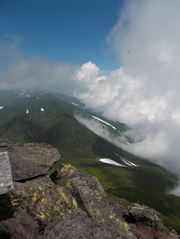 In the upper left we see clear blue sky, and in the upper right we see a column of clouds coming up.  In the left center we see a triple emerald peak, with some snowfields on the right side.  In the foreground on the left is a pile of grey rocks.