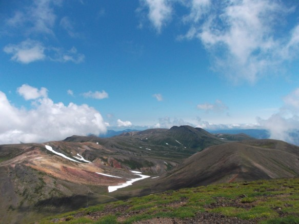 Above is a clear blue sky, with some white clouds at the edges.  Below wee see a set of green and reddish-brown hills with a valley in the center, and a little snowfield in the valley.