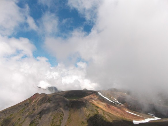 Above is a blue sky being covered with large clouds (the one clearing in the clouds is in the upper left).  Below we see a reddish-brown volcano with patches of green and a cicular crater at the top.