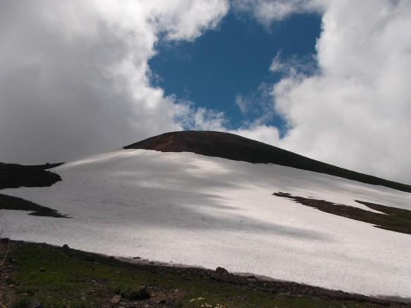 Above there are white clouds with a hole of blue sky in the center.  Below there is a mountain rising gently up in the shadow of the clouds, covered with a large snowfield like a white cape.  The snowfield is partially in the shade, partially in the sun.