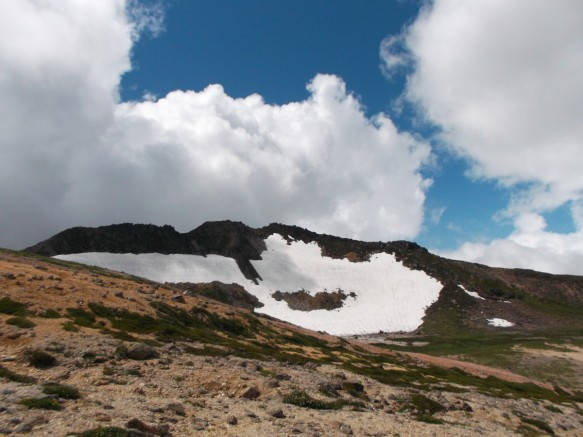 There is an opening of blue sky running from upper left to lower right; otherwise the clouds are blocking the sky.  Below we see a steep slope mostly covered with snow; otherwise it is brown.  The big cloud above is casting a partial shadow across the snow.  In the foreground is the closer side of the crater's rim, reddish-brown with tufts of green shrubs.