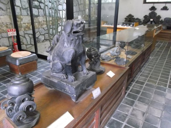 The photo shows a statue of a puppy sitting upright on its hind legs carved in stone, in a room with other sculptures with glass cases and stonework on the walls and floors