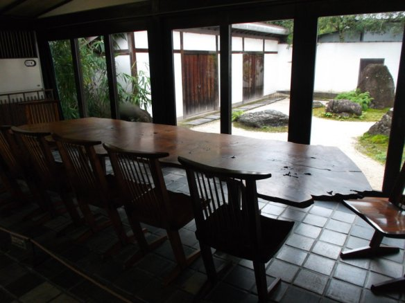 The photo shows a long, wooden table made by traditional Sanuki craftspeople, and in the background a traditional Japanese rock garden is visible