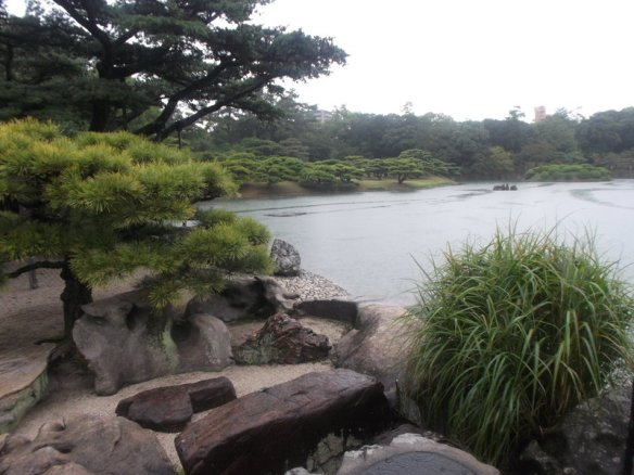 On the left side, a full-sized pine tree towers above, and a bonsai pine tree stands before it, with a group of large rocks lining the bottom of the picture.  In the upper right there is white sky, and below the white sky is a vast pond.