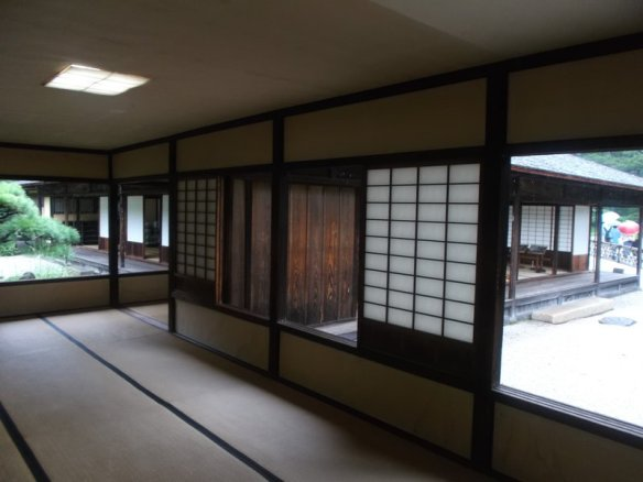 The interior of the teahouse, with the open airy room, the tatami mats on the floor, and the traidtional wooden panelling on the walls.