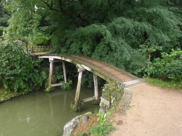 There is a simple wooden bridge crossing a brown stream with lush trees and other green plants on the other side.