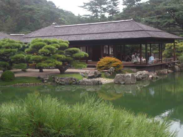 We see a rectangular Japanese-style building jutting into a pond, with bonsai pine trees on the left side.