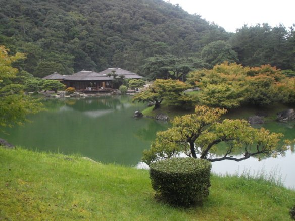 In the background of the photo is a forested hill on the left, and white sky on the right.  At the base of the hill is a teahouse, and before it is a pond.  In the lower right of the photo is a bonsai pine tree