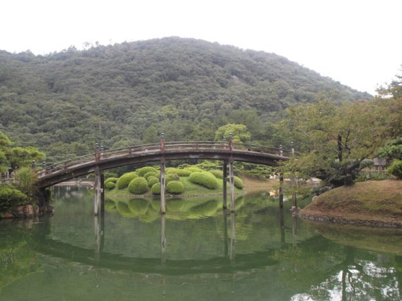 Above is a white sky.  In the background there is a hill covered with trees.  In the foreground is a gracefully curving wooden bridge, which is reflected on the surface of the pond.  Behind it, an island covered with circular little green shrubs is visible.