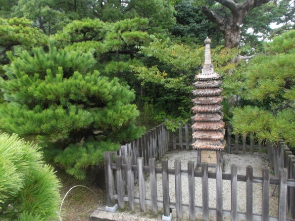 Among a bunch of bonsai pine trees, there is a small fenced off square, with gravel inside and a small eight-level pagoda made of clay