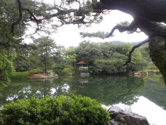 Above are pine branches against the white sky.  Below is a pond reflecting the white sky and the green trees.  On the far side is a bank with many trees and a little Japanese-style pavillion.  At the bottom of the photo is a green little bush on the left side.