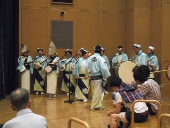 There are about ten musicians, all wearing light-blue shirts, and long, narrow pale-yellow skirts.  Most of them have white headbands, but a few are wearing the folded straw hats.  They have traditional Japanese instruments in their hands