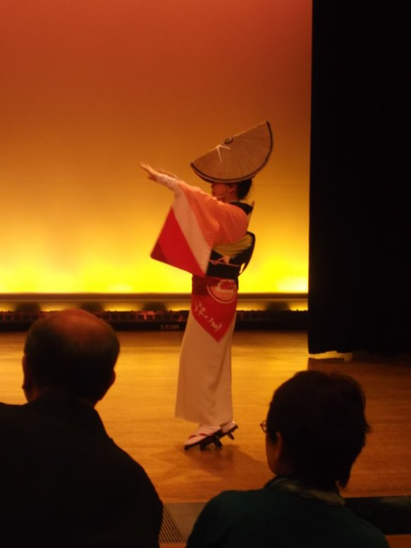 A female dancer wears a white-and-pink dress with long, draping sleeves like small, stiff flags.  On her head is a hat which looks like a circular straw hat foled in two, covering her forehead.  We see the dancer's profile, facing left.  Her left arm is raised.  Behind her, we see a background of sunset colors.