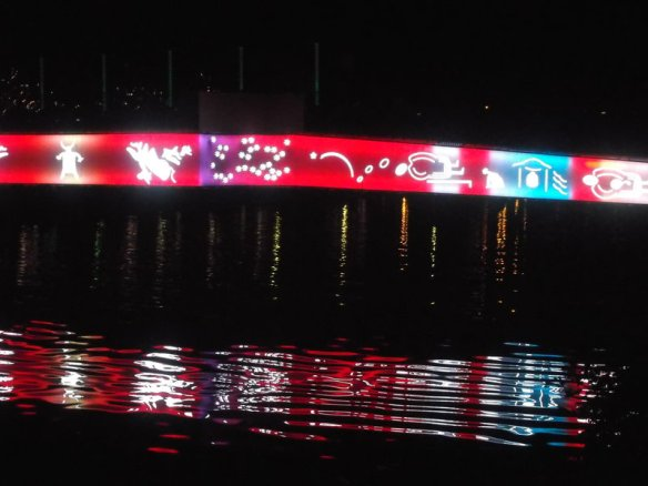 In the dark night, there is a bridge lit up with mostly pink lights, with white butterflies and a blue flower, the reflection of the bridge can be seen in the dark river water below