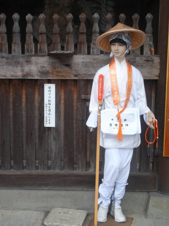 This photo shows a mannequin dressed as a henro - straw hat, walking stick, white clothes with orange thingy tied around the neck and drooping over the chest, with a set of prayer beads in one hand