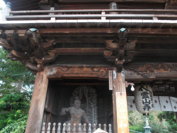 The photo shows part of the wooden gate to the temple, centering on a wooden statue of one of the Buddhist demon guardian kings