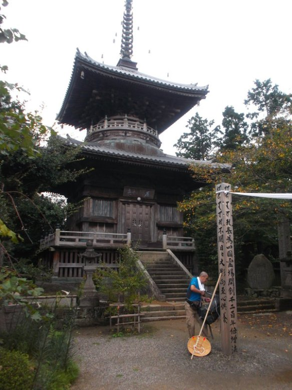 In the background is a three-story pagoda building.  In the lower right, there is a man wearing a blue shirt, with a walking stick and a straw hat on the ground beside him