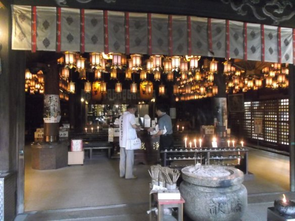 The photo shows a chamber with a ceiling full of lit up lanterns.  In the foreground at the top are a series of papers hanging down with Japanese kanji on them.  In the room there are various small statues, candles, and places to burn incense.  Two people are inside the chamber.