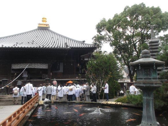 On the far side of the pond, we see a large group of people in white clothes, and behind them is a temple building