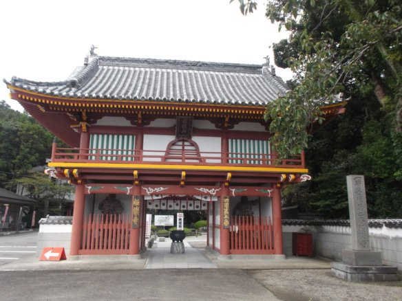 The photo shows a traditional, two story Japanese gate which is mostly covered with orange paint, with white paint in the upper center
