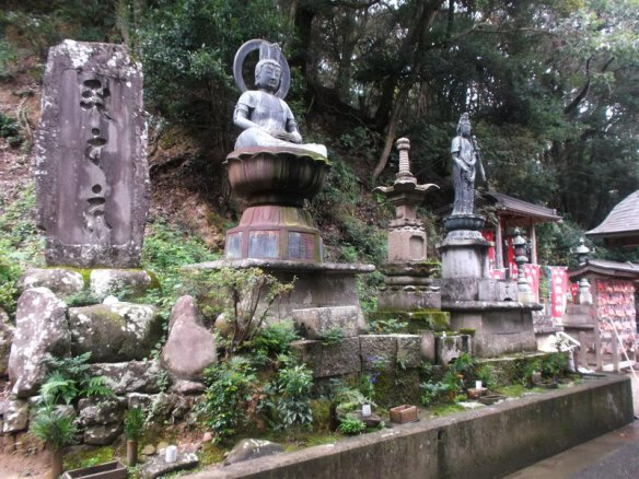 There are a bunch of mounted Buddha statues, with little green plants growing at the base, and green trees visible in the background
