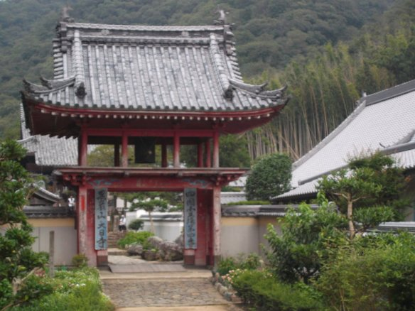 There is a two level gate to a wall compound, with a hillside covered with bamboo forest in the background