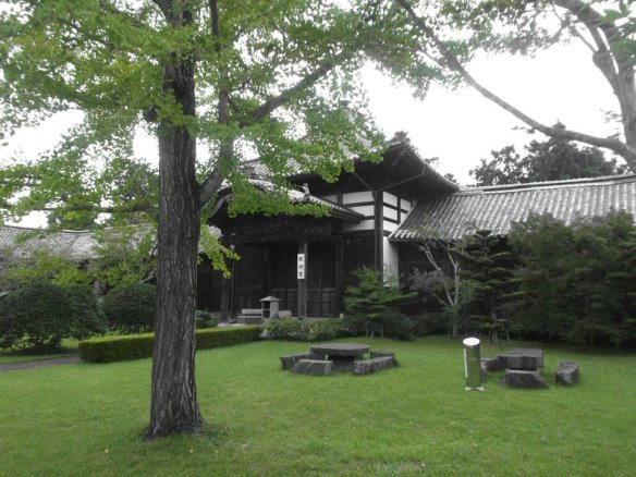 The photo is filtered so it only shows black, white, grey, and green.  There is a tall gingok tree on the left side in the foreground, there is a grassy lawn below, and behind is a wide, wooden temple structure