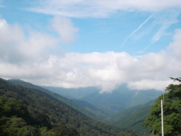 Above is a blue sky with little white puffs of clouds.  Below is a valley, flanked by green mountains on both sides, heading straight into another green mountain in the distance.  Above the distant green mountain is a blanket of white clouds