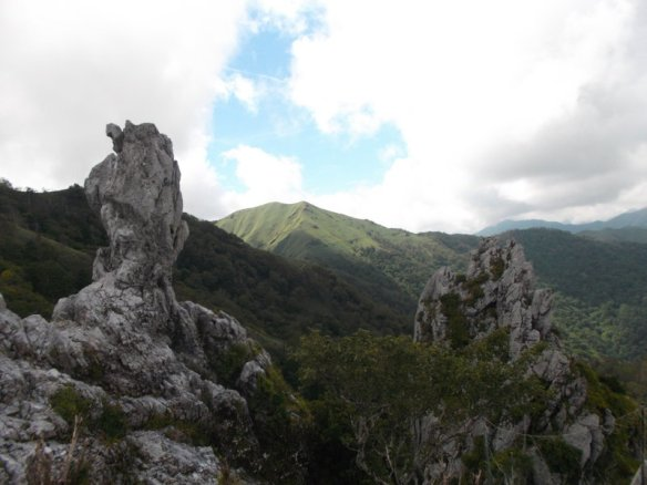 In the foreground, we see two grey, jagged rocks rise up, one on the left, one on the right.  In the background, we see the green mountains of the Iya Valley right before they get smothered with clouds.