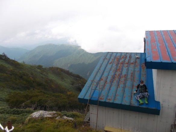 In the background, there is a blanket of white cloud smothering green mountains.  In the foreground, on the right side, is the blue metal roof of a building, and there is a man sitting on the roof.  The man looks small compared to the roof, let alone the mountains.