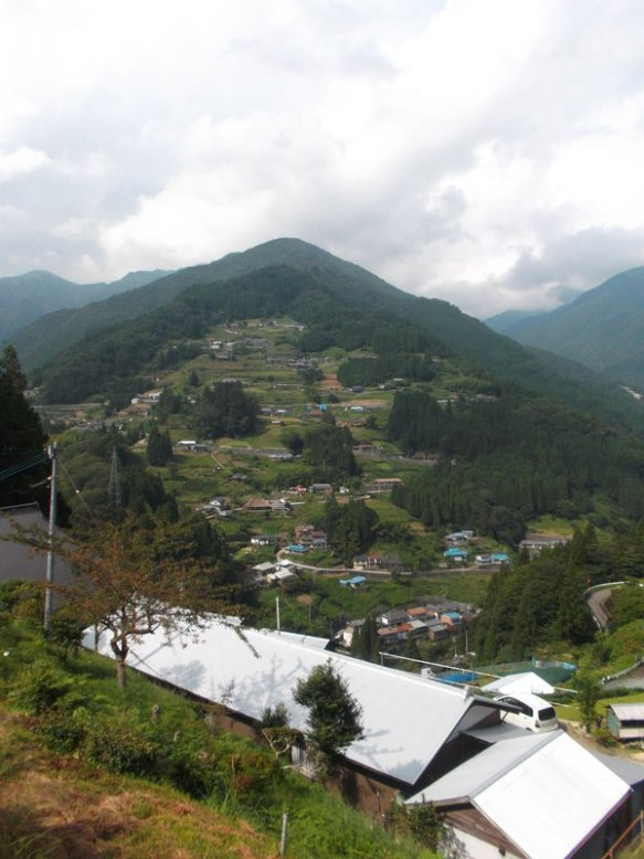 There is a tall green mountain, with a long switch-backed road creeping up its face.  Along the road is a village with many traditional Japanese farmhouses