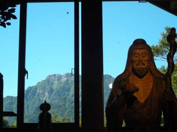 We see a wooden statue of a man in the foreground, and in the background, therough a window, we see Ishizuchi-san
