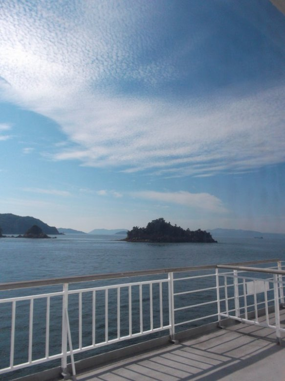 Standing on the deck of the ferry, looking at little green islands on the Seto Inland Sea.