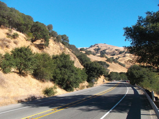 Under a big blue sky, we see hills covered with yellow dead grass with splotches of green trees on them, and a road winds around the hills in the bottom right