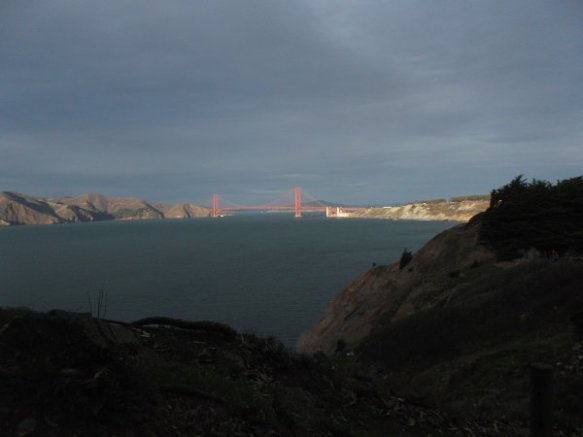 The Golden Gate Bridge is illuminated with the glow of the sunset