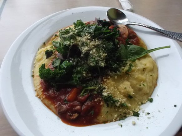 A mix of polenta and tomato sauce, topped with kale greens and vegan cheeze