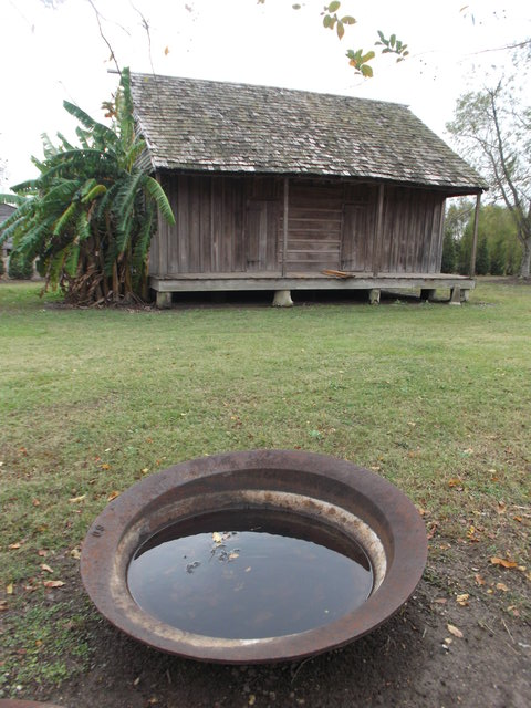 A slave cabin, and a bowl used for processing sugar cane.